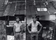 Two shirtless men standing in front of shanty, black and white