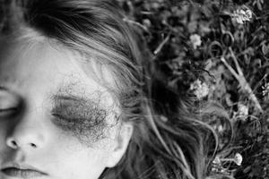 Elaine Suzanne Miller - girl's head lying on ground, eyes closed, black and white.