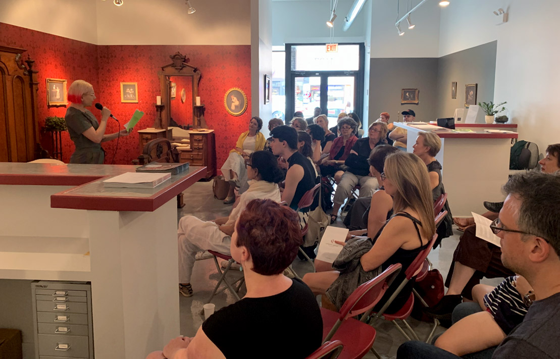 Image: Art Speaks event at Catherine Edelman Gallery. A crowd sits facing a person reading poetry.