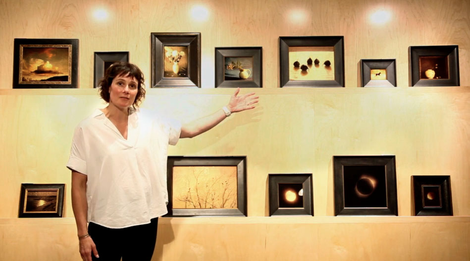 Image: Juli Lowe stands in front of a wall of framed works by Kate Breakey.