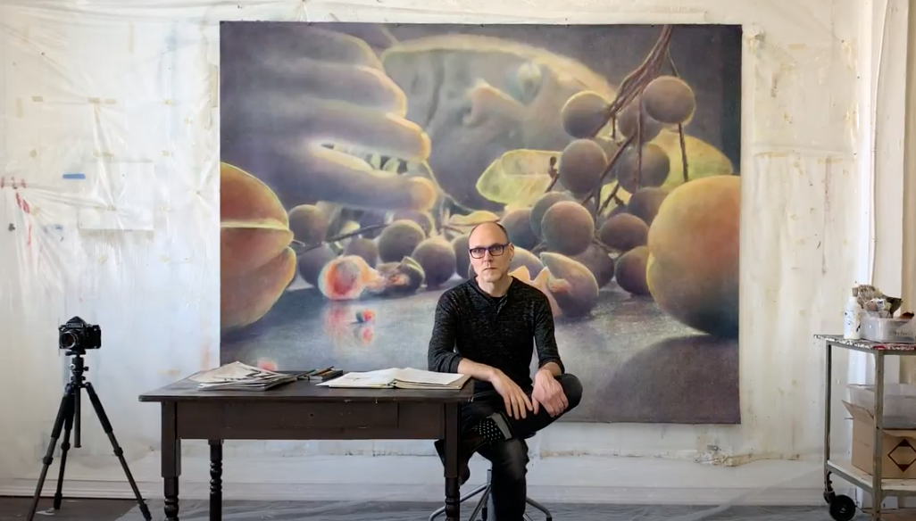 Image: Robert ParkeHarrison sits in his studio in front of a large mixed-media piece.