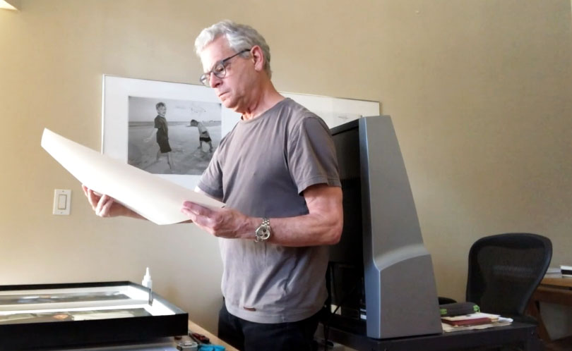 Image: Jeffrey Wolin at his home studio looking at photographs.